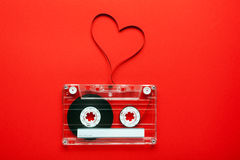 Vintage audio cassette. With loose tape shaping a heart on red background royalty free stock photography