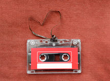 Vintage audio cassette with loose tape shaping a heart on red background Royalty Free Stock Images