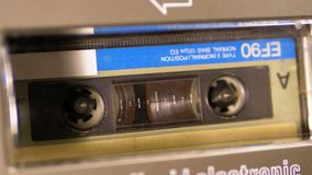 Vintage Audio Cassette in the Tape Recorder Playing and Rotates. Macro. Vintage audio cassette tape with a blank label used for sound recording in a retro stock video