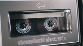 Vintage Audio Cassette in the Tape Recorder Playing and Rotates. Macro. Vintage transparent audio cassette tape with a blank label used for sound recording in stock video