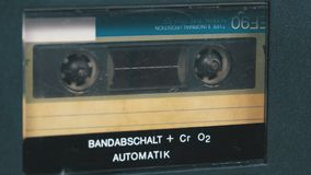 The vintage audio cassette in the tape recorder rotates. Macro static camera view of a vintage audio cassette tape with a blank label in use sound recording in stock video footage