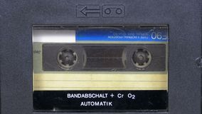 The vintage audio cassette in the tape recorder rotates. Macro static camera view of a vintage audio cassette tape with a blank label in use sound recording in stock footage