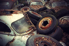 Vintage Auto Graveyard. Rusty wheels and autumn leaves lying on vintage cars in an old auto graveyard Stock Images