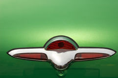 Vintage auto ornament. Closeup of a decorative shield on the surface of a green vintage automobile Royalty Free Stock Images