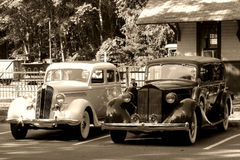 Vintage Automobiles at an Antique Train Station. Two old vintage automobile cars at an antique train station in retro sepia Stock Images