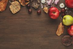 Vintage autumn border from apples and leaves on wooden table. Vintage autumn border from apples, chestnuts and fallen leaves on wooden table with copy space for stock images