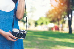 Vintage autumn photo with girl standing in a park with old camera. Stock Photo