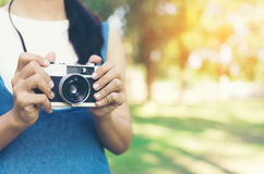 Vintage autumn photo with girl standing in a park with old camera. Stock Photos