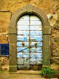 Vintage door, lions and history in Civita di Bagnoregio, town in the province of Viterbo, Italy. Vintage azure door, lions and history in Civita di Bagnoregio stock images