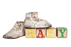 Vintage baby blocks and booties. Vintage boy baby booties and wooden blocks spelling BABY isolated on white stock illustration