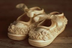 Vintage baby shoes on wood background stock photos
