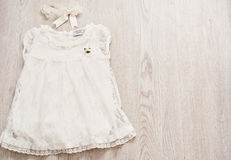 Vintage Baby White Lace Dress and Bow Headband on a Light Gray Wodden Background. Top View, Copy Space Stock Photo