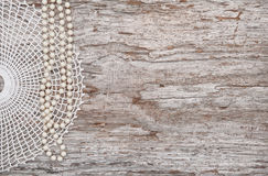 Vintage background with bead necklace and lace on the old wood. Vintage background with bead necklace and lace on the old rude wood stock photography