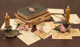 Vintage background with books, photo and candles. Vintage background with old books, postcards, candles and flowers Royalty Free Stock Image