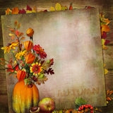 Vintage background with a bouquet of autumn leaves and berries in a vase from pumpkin Stock Photography