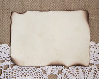 Vintage background. Burlap background with crochet lace and old burned paper Stock Photos