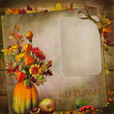 Vintage background with card,  bouquet of autumn leaves and berries in a vase from pumpkin Royalty Free Stock Images