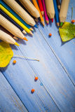 Vintage background colored pencils autumn fruits blue table Royalty Free Stock Images