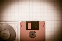 Floppy disks and mini-CD. Vintage background - computer floppy disks and mini-CD on the blueprint paper, toned Royalty Free Stock Photos