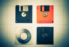 Floppy disks and mini-CD. Vintage background - computer floppy disks and mini-CD on the blueprint paper, toned Stock Image