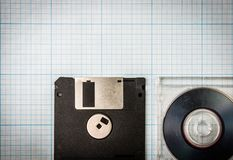 Floppy disks and mini-CD. Vintage background - computer floppy disks and mini-CD on the blueprint paper, toned Royalty Free Stock Photography