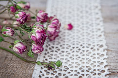 Vintage background with dry tea roses on lace and burlap Royalty Free Stock Photos