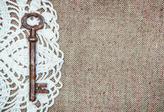 Vintage background with lacy and old key on burlap texture Stock Photography