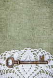 Vintage background with lacy and old key on burlap texture Royalty Free Stock Image