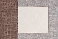 Vintage background with old paper on rude fabric and burlap Royalty Free Stock Photography