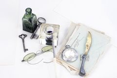 Vintage background with old pocket watch, old ink pen, handwritten letters and old ink pot. On white stock photos
