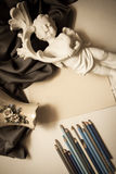 Vintage background with pencils and sculpture Stock Photos