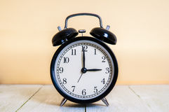 Vintage background with retro alarm clock 3pm am on wooden table Stock Images