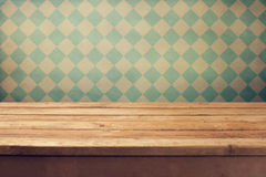 Vintage background with wooden deck table over retro wallpaper