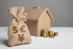 Vintage bag with dollar, euro and yuan sign and yellow coins on the background of the craft figure of the house. Home insurance stock image