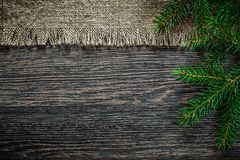 Vintage bagging pine branch on wooden board Christmas background Stock Photography
