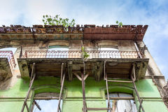 Vintage balconies. Old vintage building with green walls and balconies under blue sky Royalty Free Stock Photography