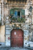 Vintage balcony with different flowers, cracked plaster and wooden doors, Mediterranean style Stock Photography
