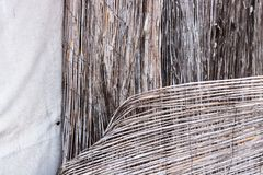 Vintage bamboo rattan close-up of a dilapidated retro worn fence held together with rusted wire and white fabric canvas background royalty free stock photography