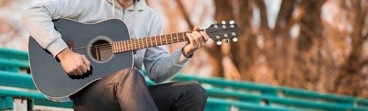 Vintage banner for site header with young man playing guitar. Music concept stock images