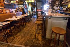 Vintage bar stools and retro style furniture of old beer cafe waiting for drinkers at evening Stock Photos