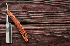 Vintage barber shop straight razor tool on wooden background Royalty Free Stock Image