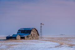 Vintage barn, bins and windmill surrounded by snow under pink sunset sky in Saskatchewan