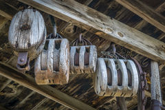 Vintage barn wooden pulleys. Vintage wooden pulleys in an old barn or workshop royalty free stock images