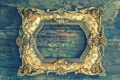 Vintage baroque golden frame on wooden background. Grunge textur Royalty Free Stock Image
