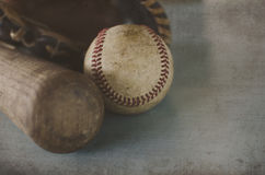 Vintage baseball bat and old ball, with leather glove in background. Royalty Free Stock Images