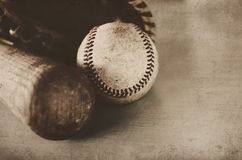 Vintage baseball bat and old ball, with leather glove in background. Royalty Free Stock Image