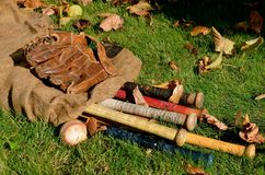 Vintage Baseball equipment. A gunny sack of baseball bats, a ball, and glove are lying on the grass surrounded by colorful leaves Stock Photography