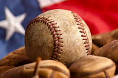 Vintage baseball, glove and American flag. A vintage baseball and glove with American flag in the background Stock Photography