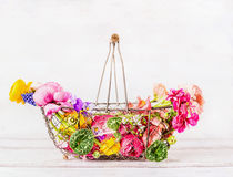 Vintage basket with various colorful garden flowers at white wooden background, front view. Summer gardening. Concept Stock Photo