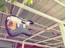 Vintage bass guitar adorns the entrance to the music store stock photo